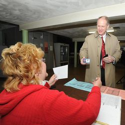 Congressman Mark Critz shows his ID to Kelly Swanson, minority inspector at precinct 17-2, as he prepares to vote in primary elections, at St. Patrick's Church Hall, in Johnstown, Pa. Tuesday, April 24, 2012. In the newly created 12th District north and east of Pittsburgh, Democratic U.S. Reps. Jason Altmire and Critz are fighting to be the last one standing after the Legislature and governor approved new lines combining their previously separate districts.
