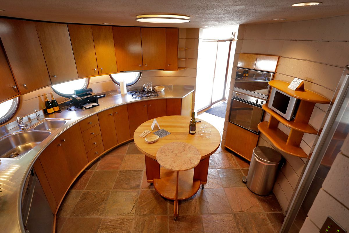 A curving circle kitchen with slate floors, wood cabinets, and stainless steel counters.