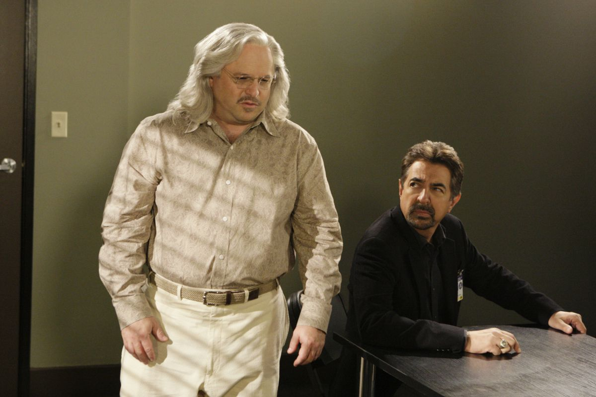 Jason Alexander in a horrible white wig in an interrogation room on Criminal Minds, with David Rossi (Joe Mantegna) sitting at a table behind him