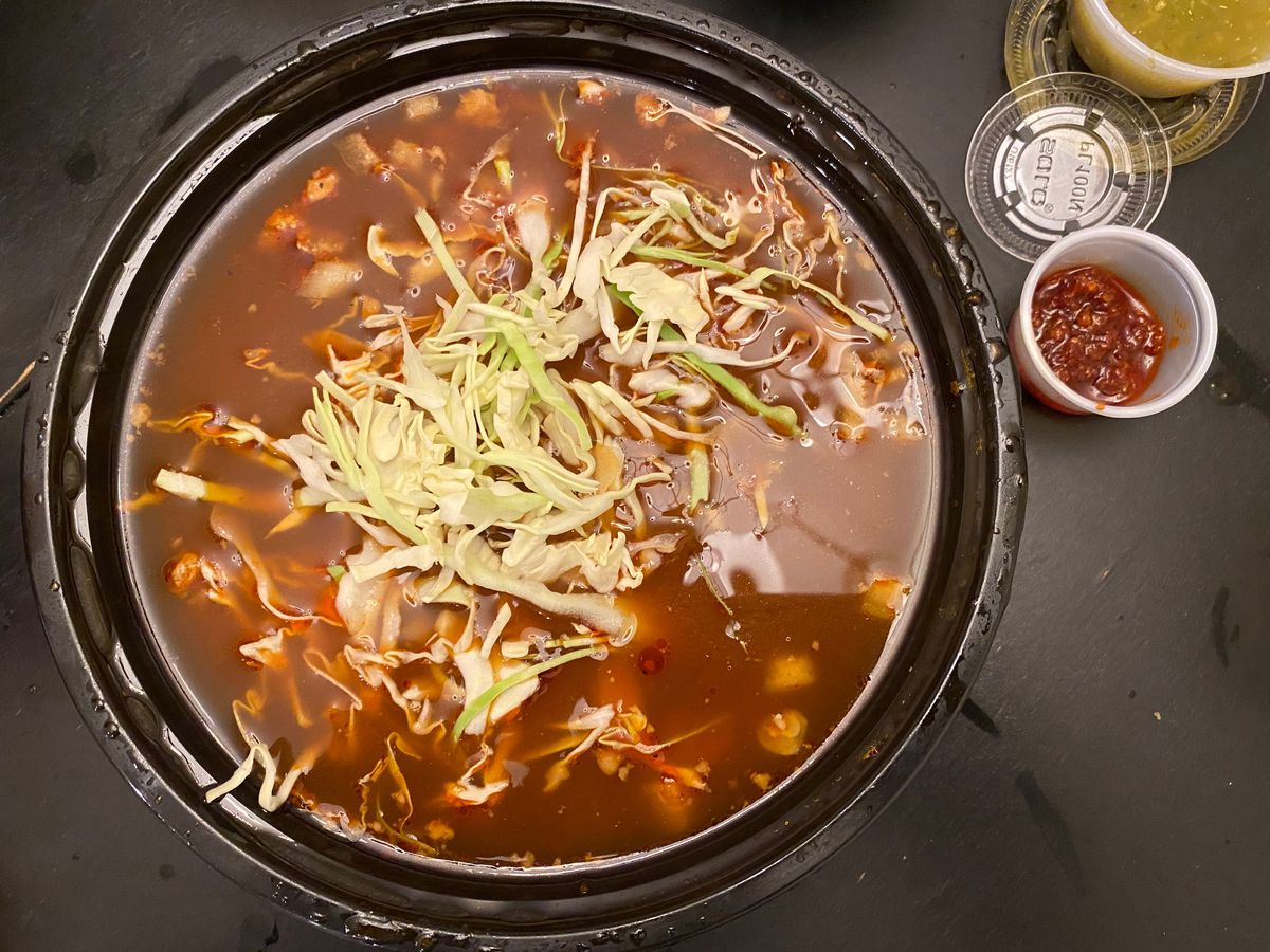 A bowl of red pozole topped with shredded cabbage with a tub of red salsa macha on the side