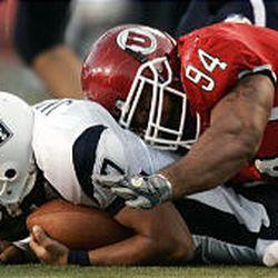 Utah defensive lineman Steve Fifita (94) falls on top of Utah State quarterback Leon Jackson in Utah's win over Utah State Saturday in Salt Lake.