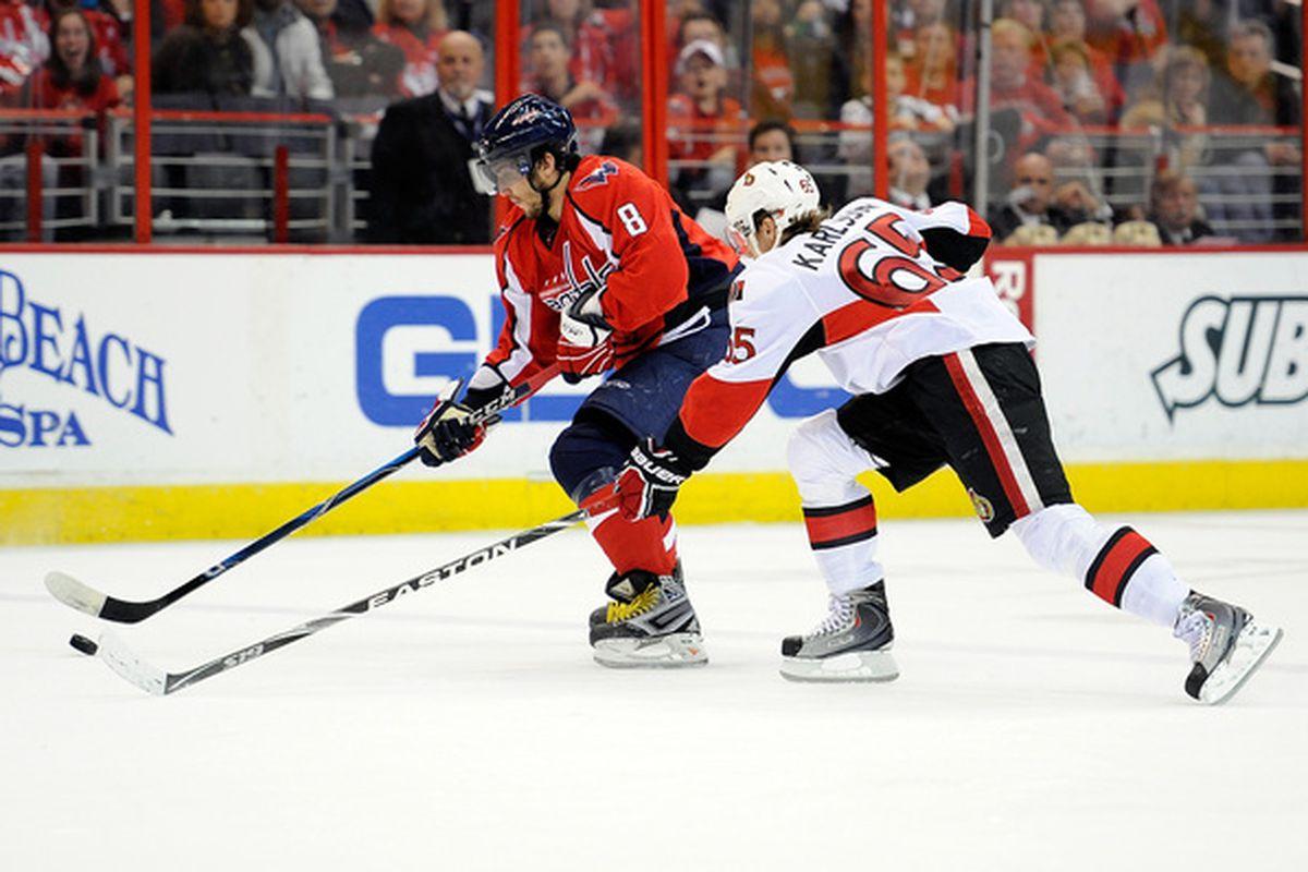 Alex Ovechkin protects the puck from big-bodied shutdown defenseman Erik Karlsson