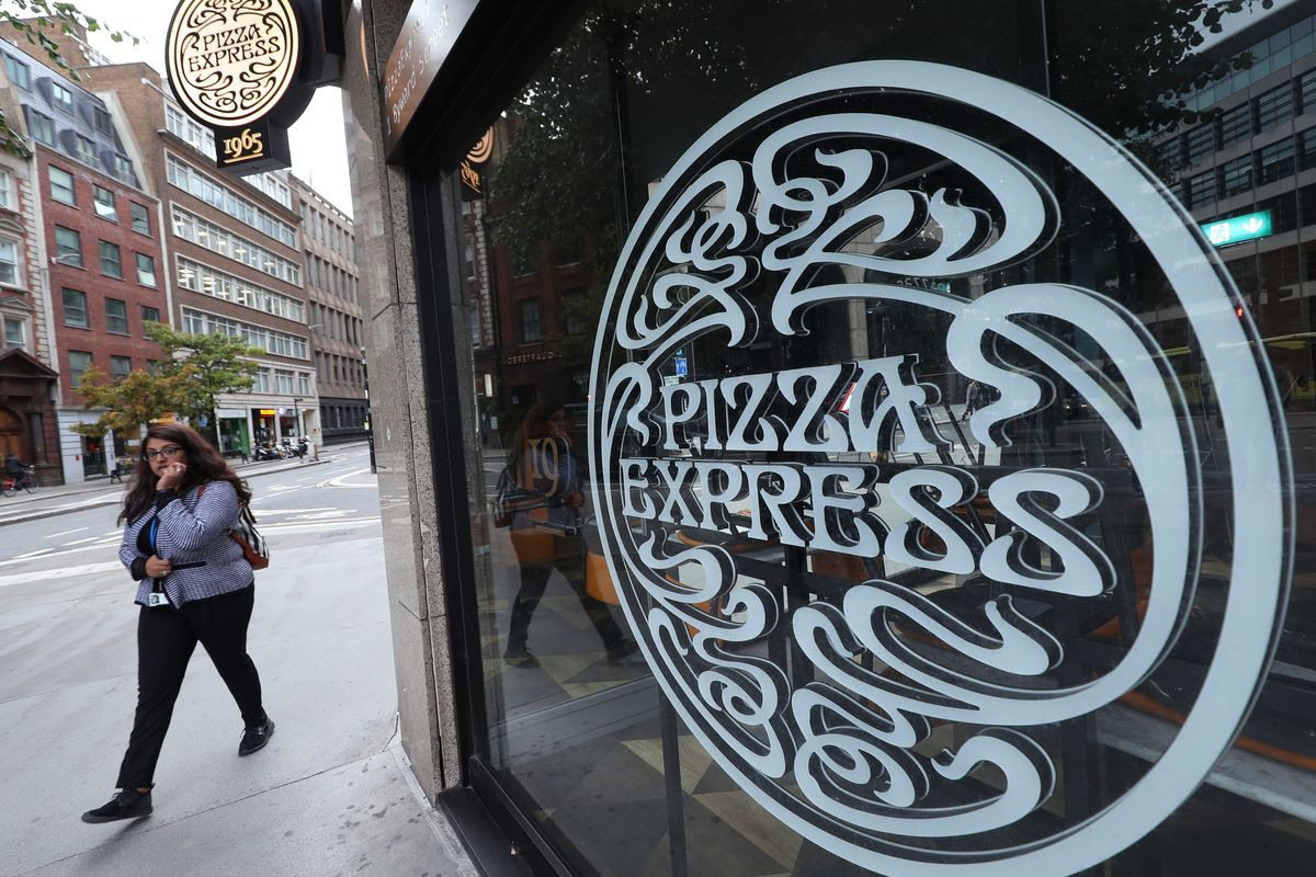 Pizza Express logo large in the foreground as a passer-by walks past, in the City of London
