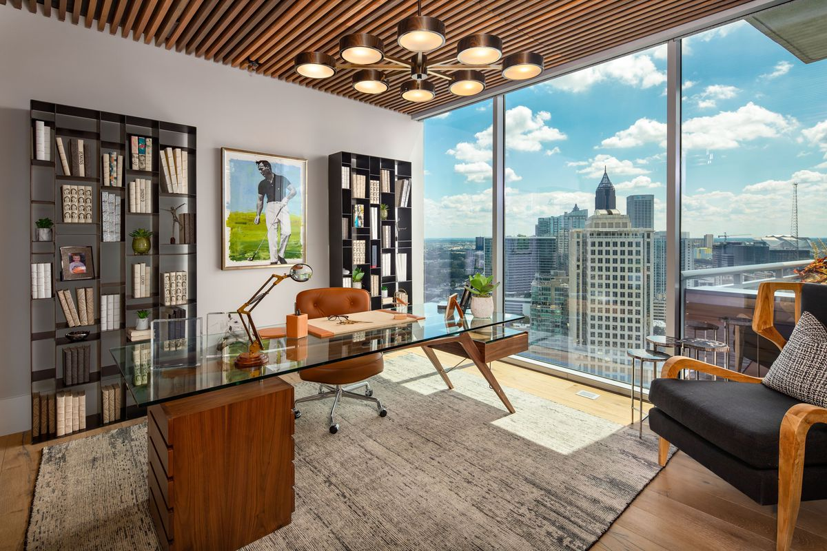 A private office with a dramatic light fixture and views across Atlanta.