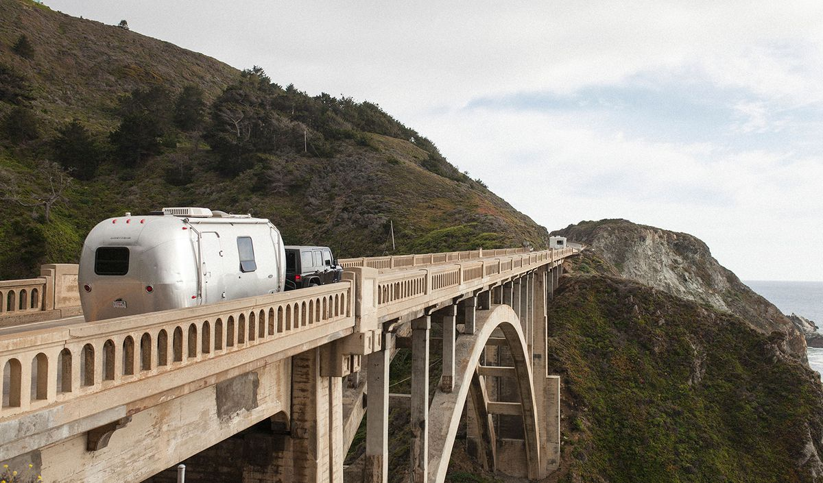 An aluminum-sided Airstream trailer travels over a tall stone bridge in the hills with rocks and the ocean in the distance.