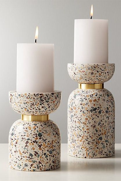 Two terrazzo-print pillars with column-like white candles on top.