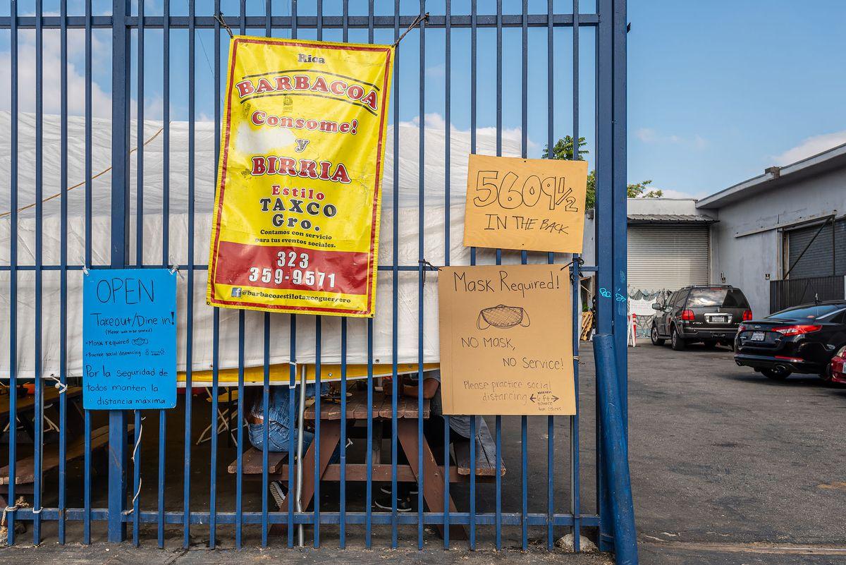在塔斯科公司外面,有红色字体的黄色标志和手写的硬纸板。在加州的洛杉矶。