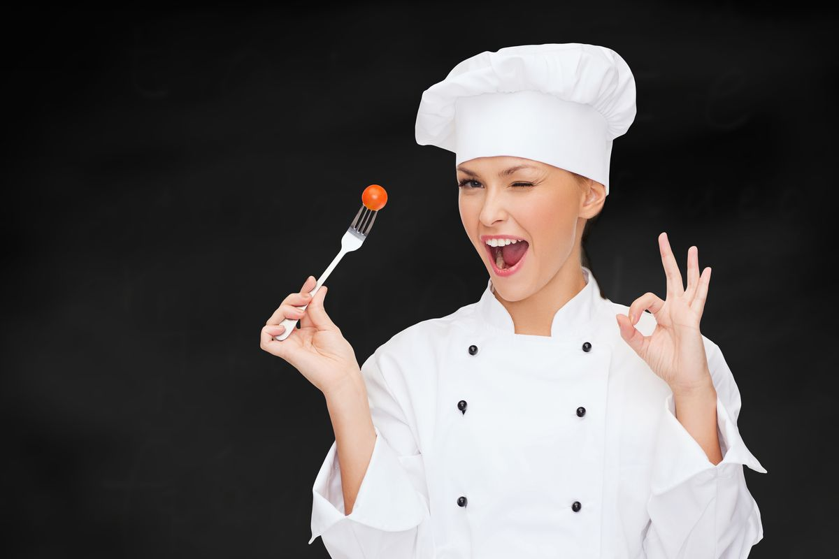 """A woman in a chef's coat and hat winks at the camera and makes an """"OK"""" sign with her hands"""