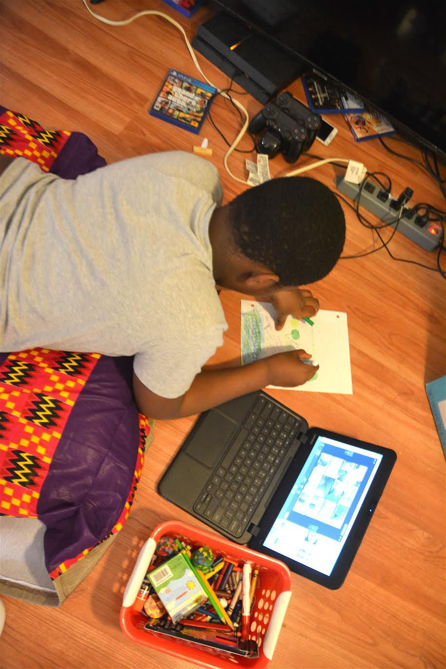 Aunullah Mohammed lies down on the pillow bed handmade by his mother, while attending class on his laptop.