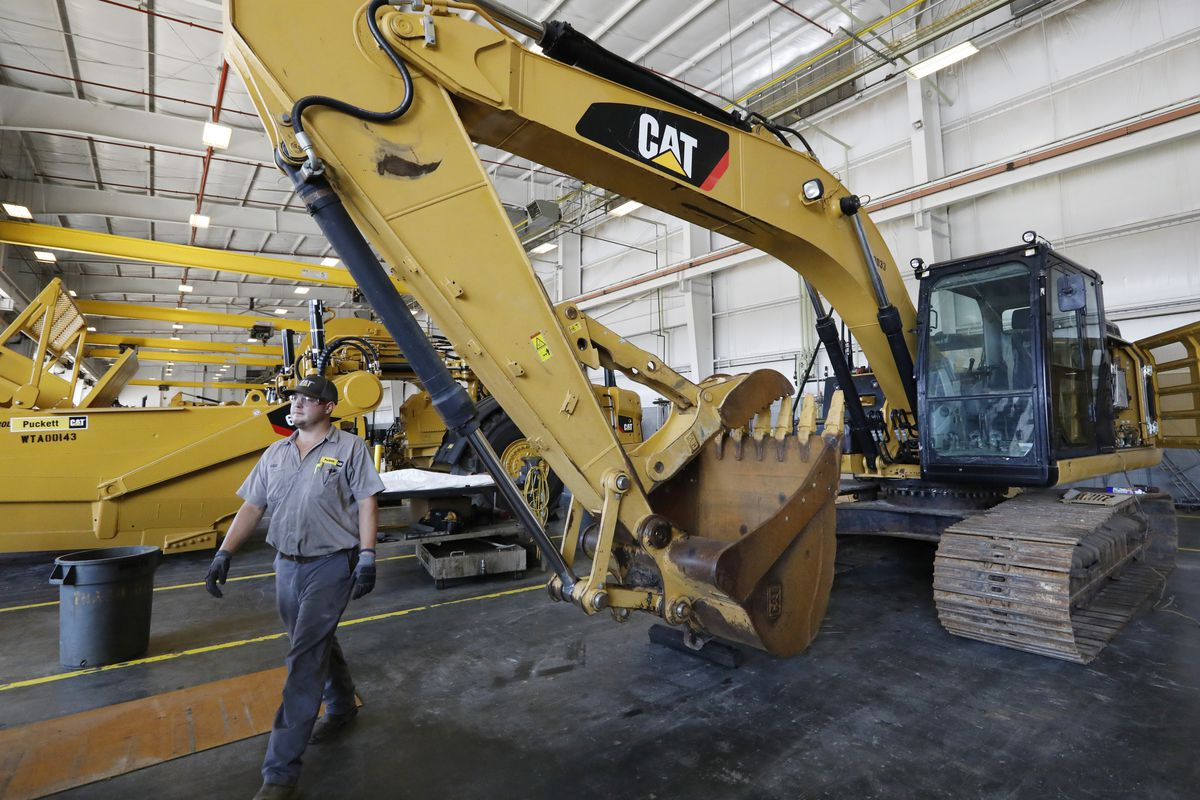 A Puckett Machinery Co. technician walks past a new heavy-duty Caterpillar excavator that awaits modification in Flowood, Mississippi.