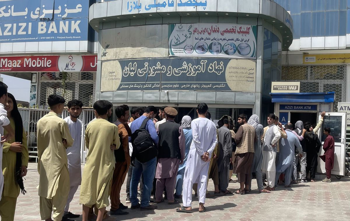 A long line of people mostly dressed in the typical caftan-style outfits of Kabul waiting outside of a grey building.