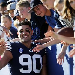 Brigham Young Cougars defensive lineman Corbin Kaufusi takes a photo with fans following NCAA football against the San Jose State Spartans in Provo on Saturday, Oct. 28, 2017.