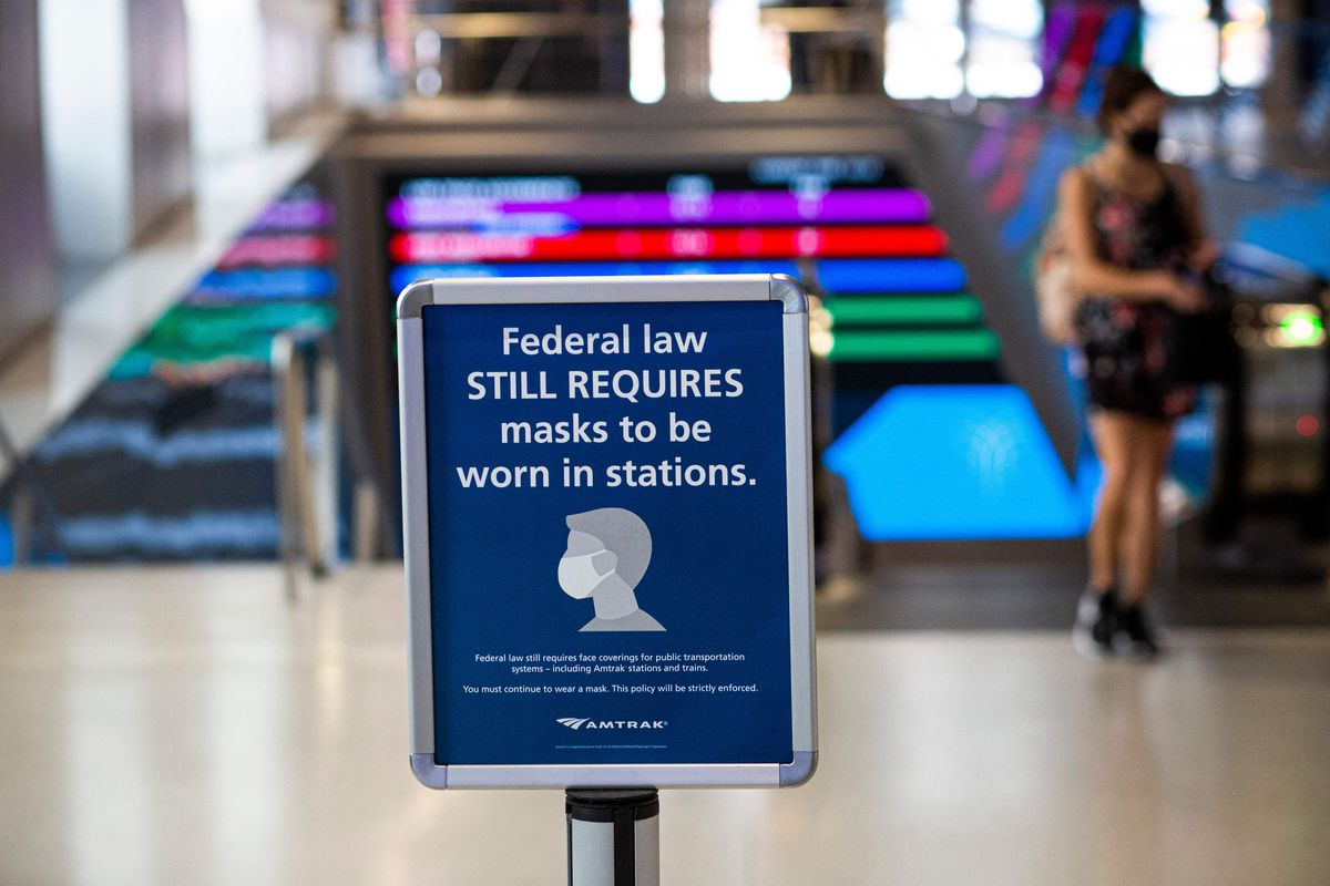 """A woman in Penn Station walks past a sign that reads, """"Federal law still requires masks to be worn in stations."""""""