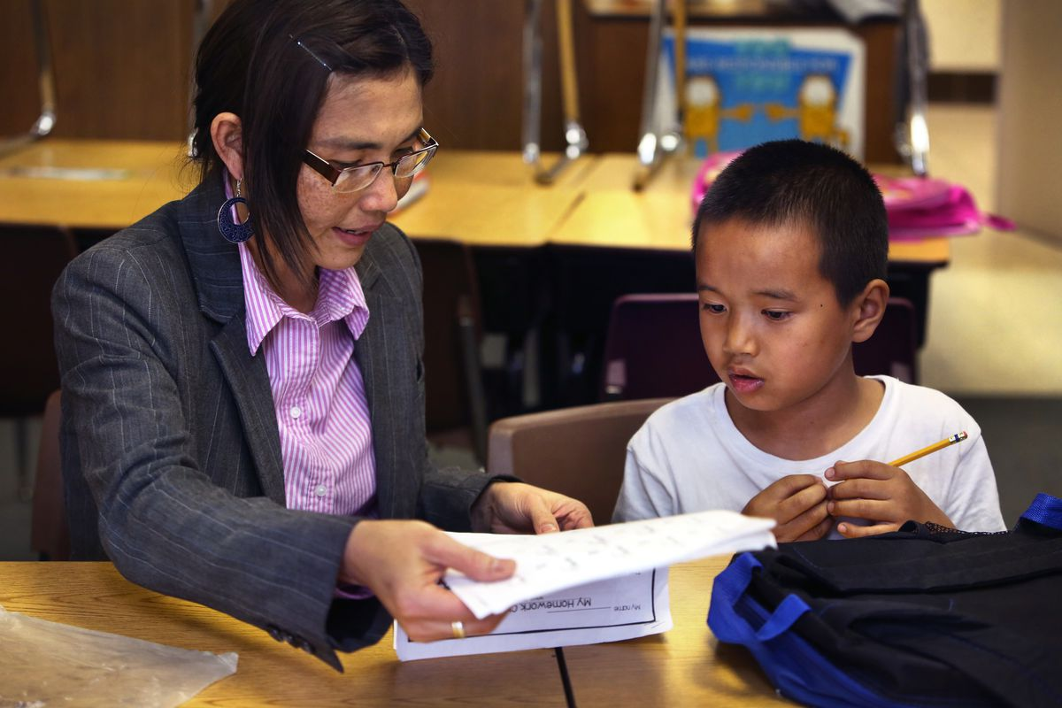 May Oo Mutraw, president of the Burmese Community Center for Education, works on spelling with Ngae Reh, 6, at the BCCE after-school learning time at Nora Elementary School in Indianapolis.