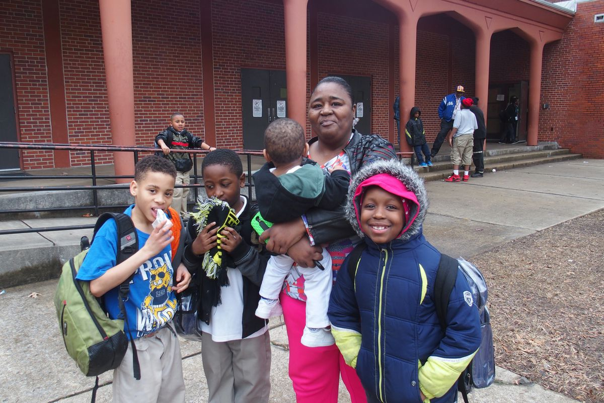 Anita Smith stands with grandson Jaylan Jones (second from left) and his friends in front of Lincoln Elementary School during its last months of operation in 2015. Shelby County Schools is tracking the academic performance of displaced Lincoln students who now attend A.B. Hill Elementary.