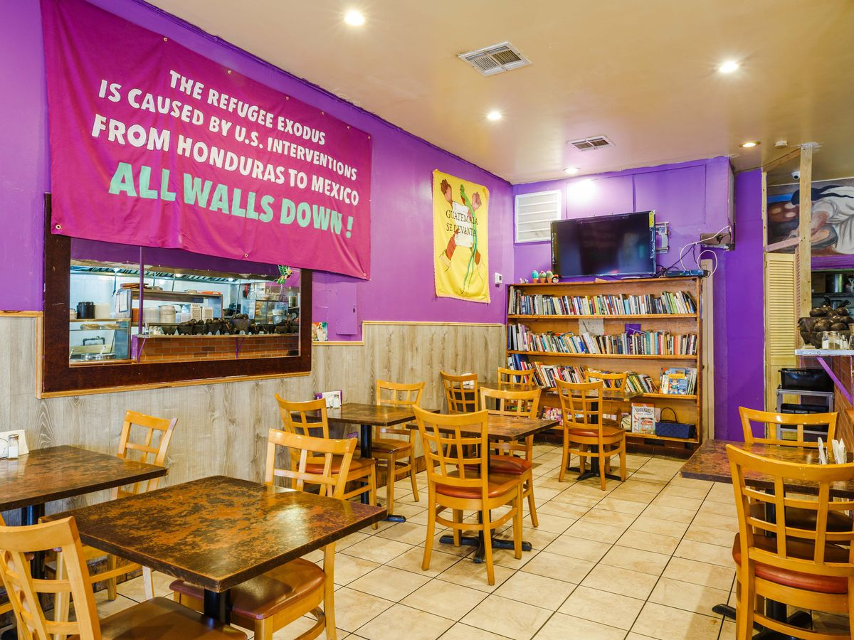 """La Morada's dining room has wooden tables and chairs, purple walls, and a hanging poster saying """"all walls down"""""""