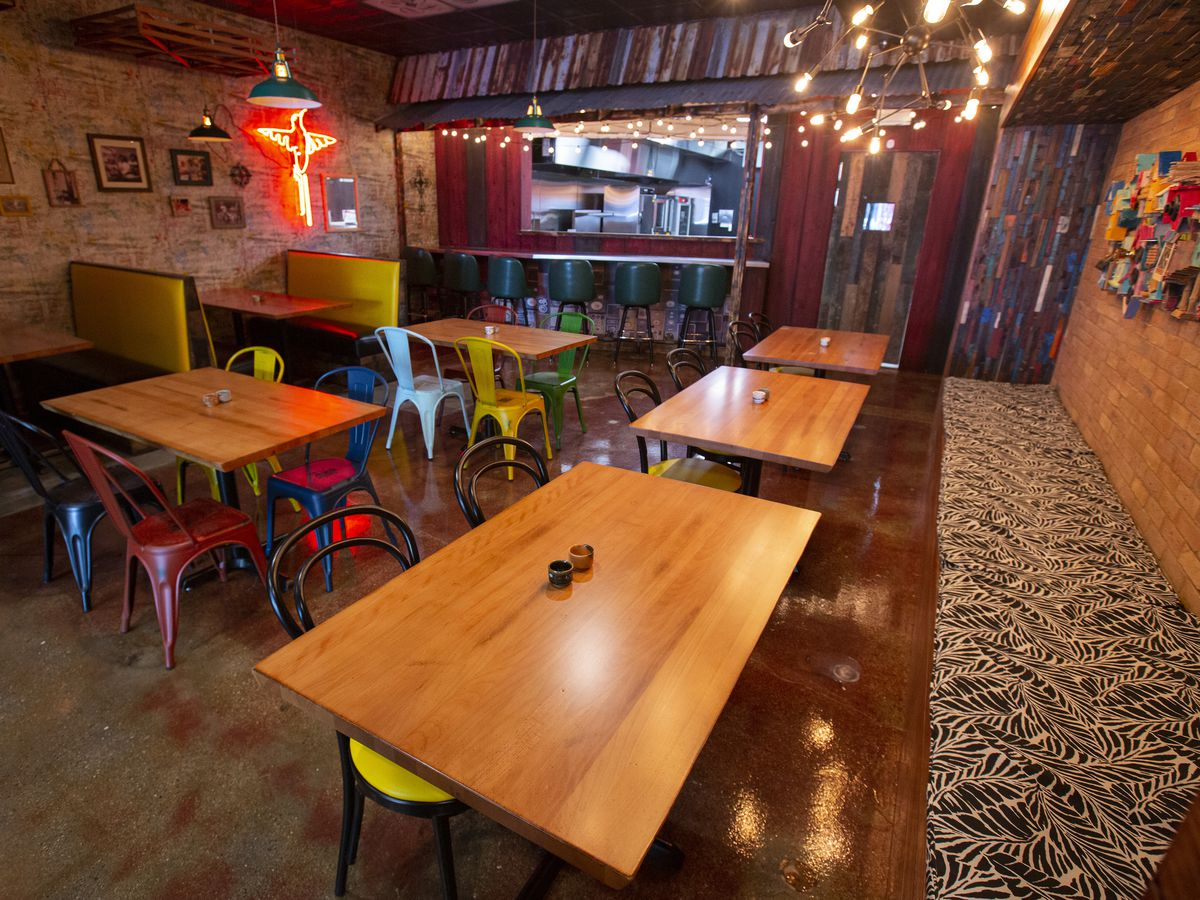 A colorful restaurant with tables, neon lights and more.