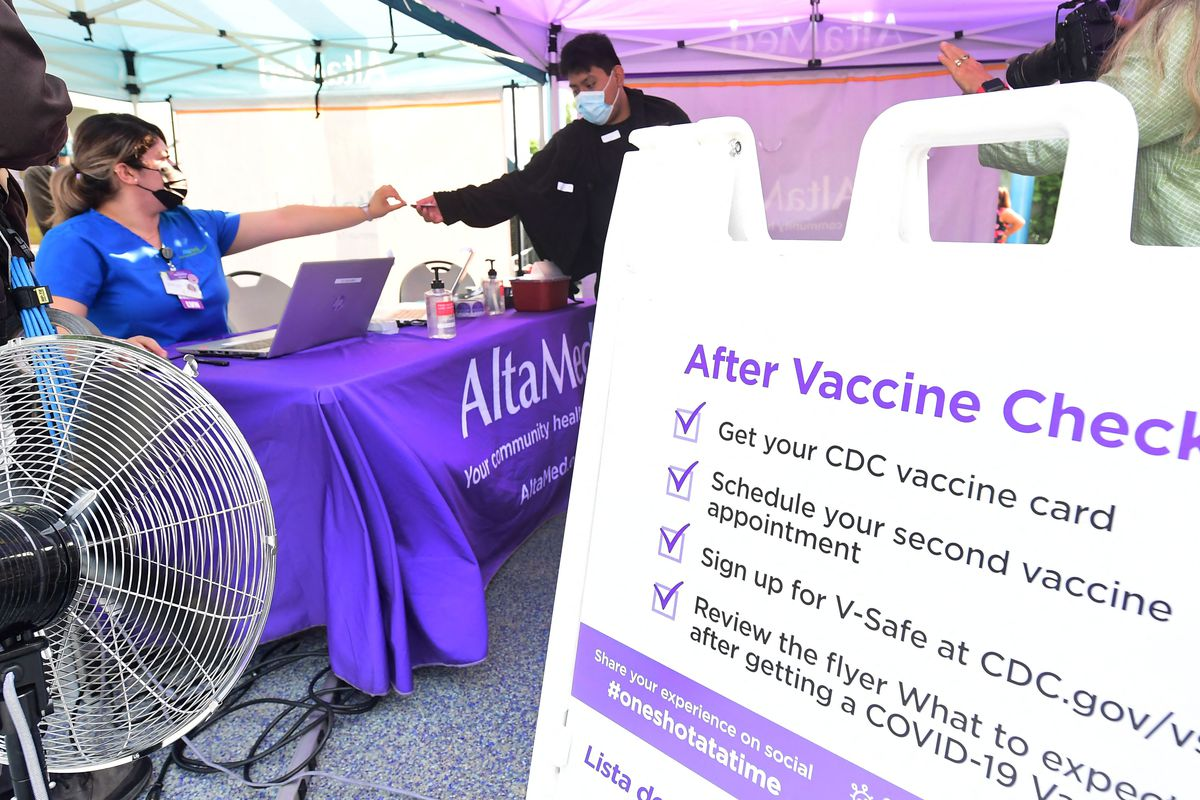 A nurse from AltaMed Health Services hands out the vaccine card to people after receiving their COVID-19 vaccine in Los Angeles on Tuesday.