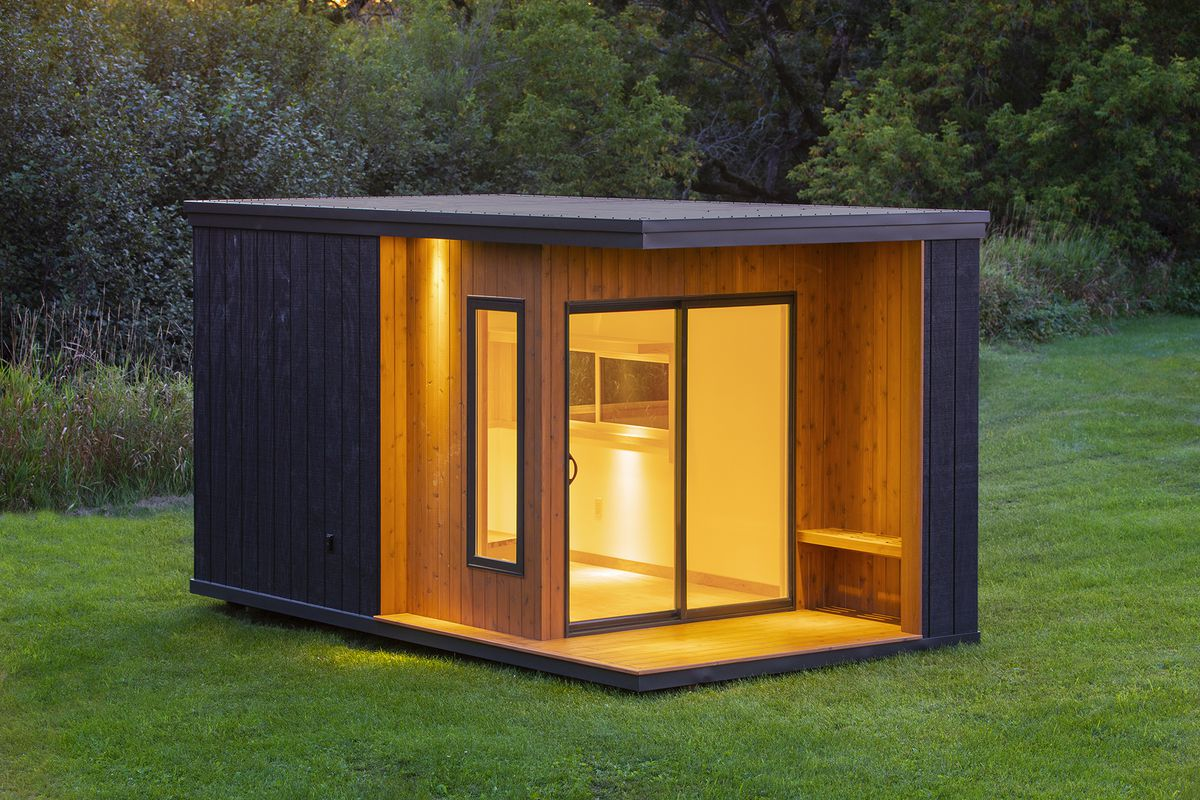A small boxy dwelling sits on a grassy plot. It is clad in black and natural wood, with a small covered porch and sliding glass doors to the inside.