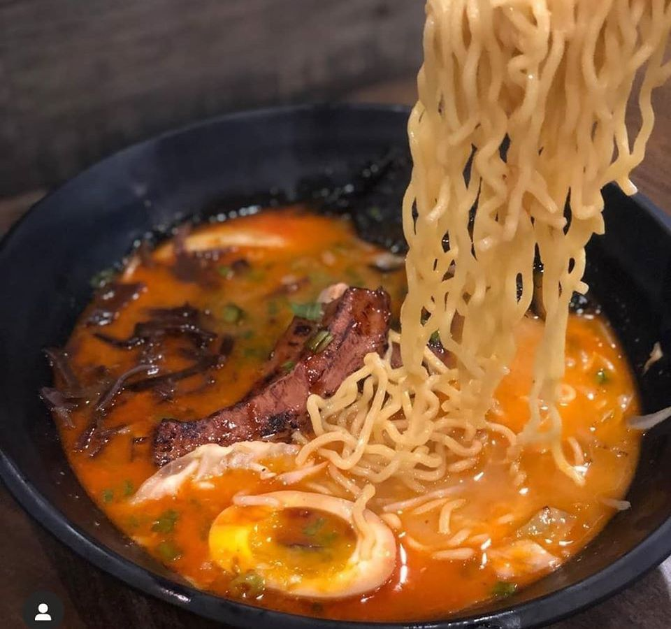 Noodles being pulled from a bowl of ramen
