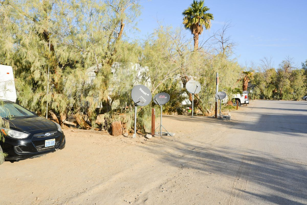 A dirt path showing parking spots for RVs in the desert.