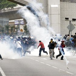 Protesters run as riot police fire tear gas at demonstrators during a anti Internal Security Act (ISA) protest near the National Mosque in Kuala Lumpur, Malaysia, Saturday.