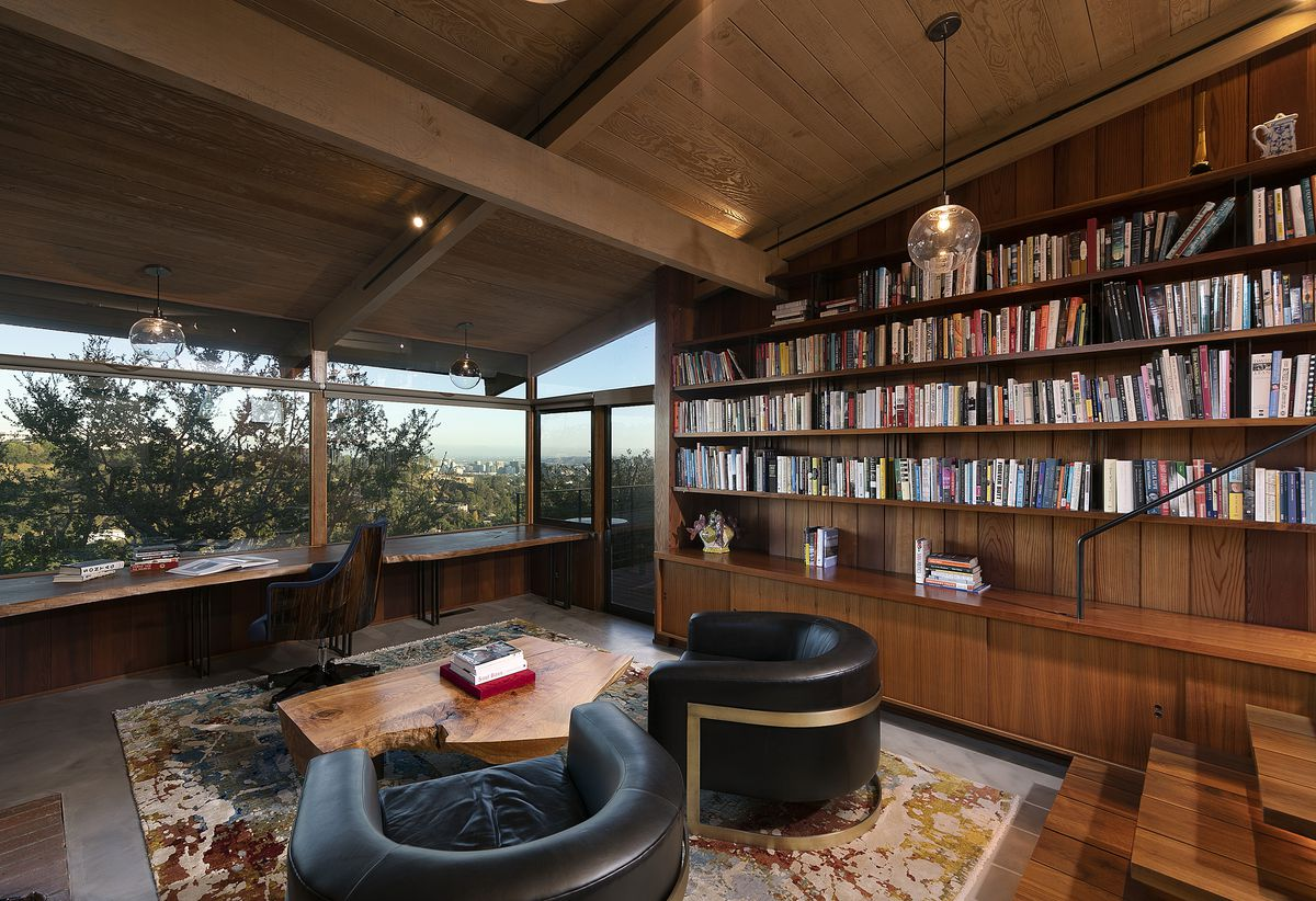 The library is lined with wood shelves and wood beamed ceilings. It has one large wall of glass and concrete floors.