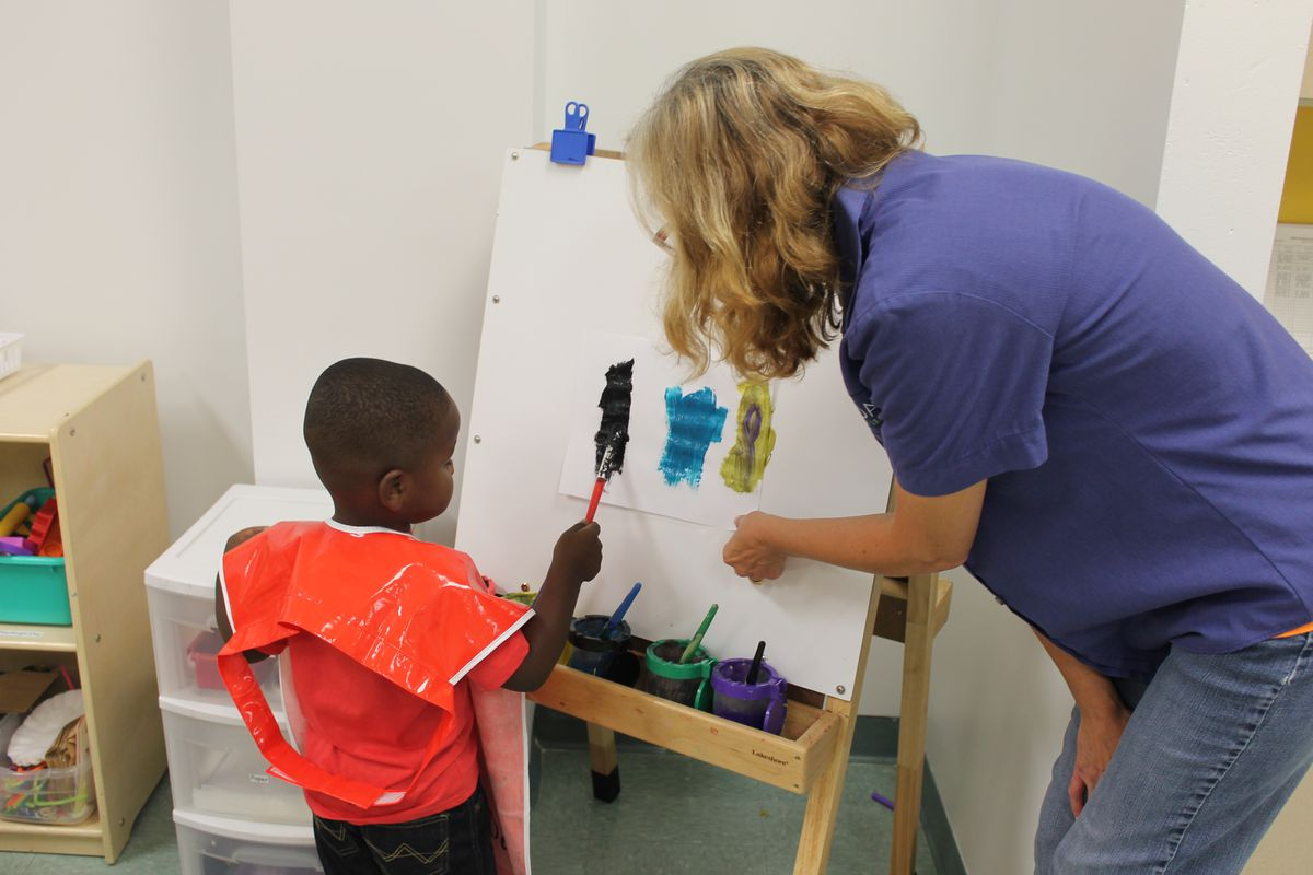 Norma Callahan, lead teacher, assists a preschooler painting at an easel in a preschool classroom at Day Early Learning at Eastern Star Church.