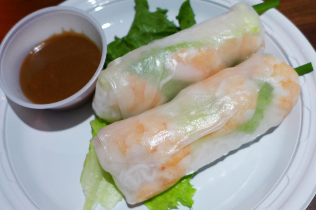 A pair of shrimp summer rolls with the shrimp visible through the diaphanous rice paper.