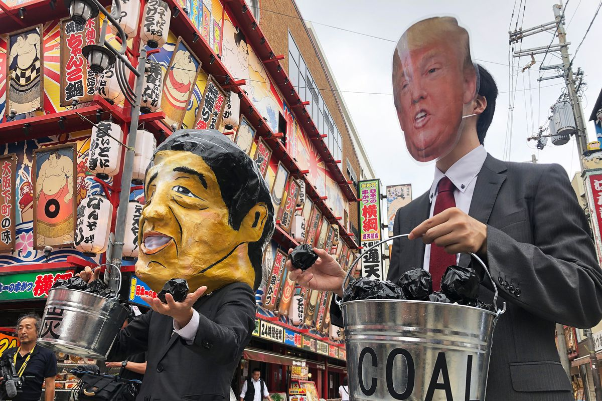 Protesters wearing masks of world leaders including a giant paper mache Japanese Prime Minister Shinzo Abe (L) and US President Donald Trump demonstrate against climate change and coal use as world leaders convene at the G20 summit in Osaka on June 28, 2019.