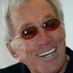 FILE - U.S. singer Andy Williams smiles as he speaks to reporters during his news conference at a Tokyo hotel, in this July 25, 2004 file photo. The Branson Tri-Lakes News reports the 83-year-old Williams told the crowd at his Christmas show Saturday night Nov. 5, 2011 at the Moon River Theatre in Branson, Mo., that he is battling bladder cancer.