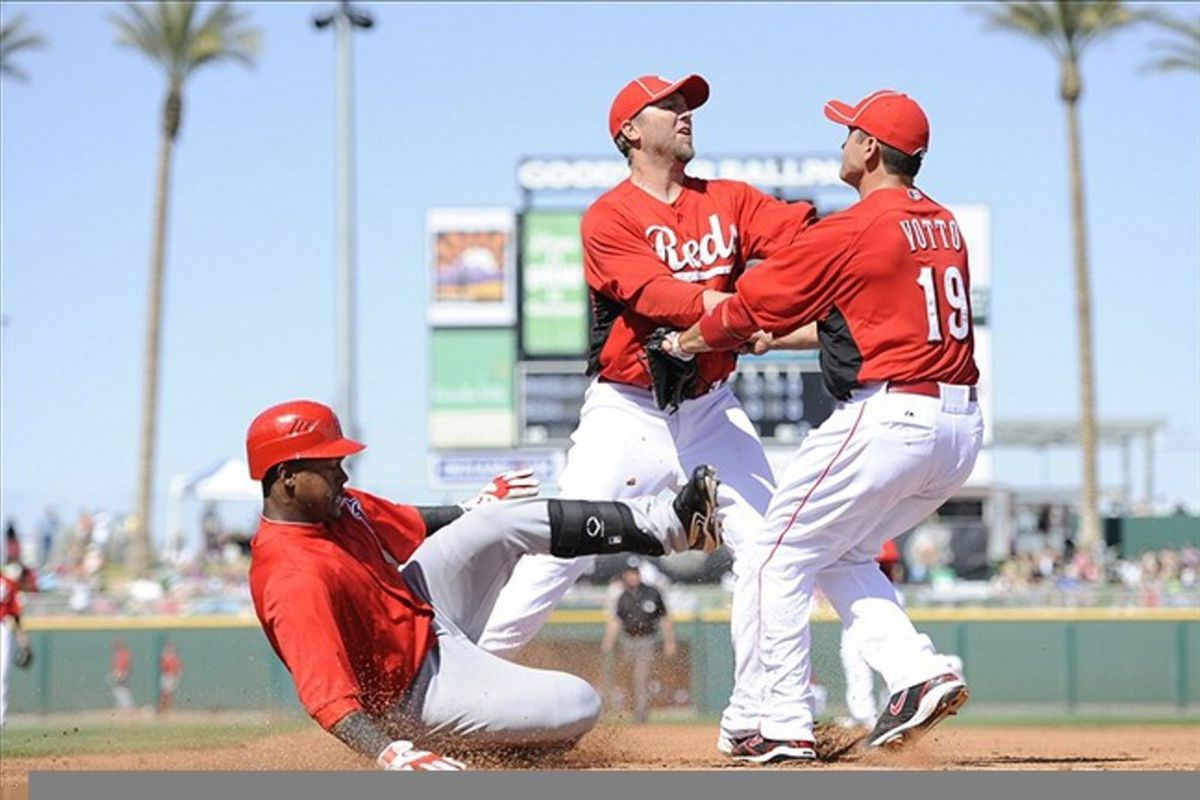 Cincinnati Reds first baseman Joey Votto (19) and starting pitcher Brett Tomko (36) miss on an attempt to get out Los Angeles Angels shortstop Jean Segura (20) during the fourth inning at Goodyear Ballpark.