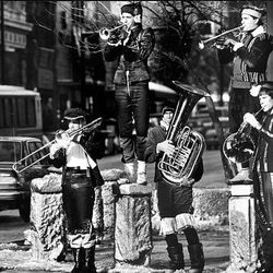Braving bitter cold temperatures, musicians Dave Spencer, Dave Wick, Mark Robinette, Michael Huff and Mark McCullough serenade Christmas Eve shoppers on Main Street in 1987.