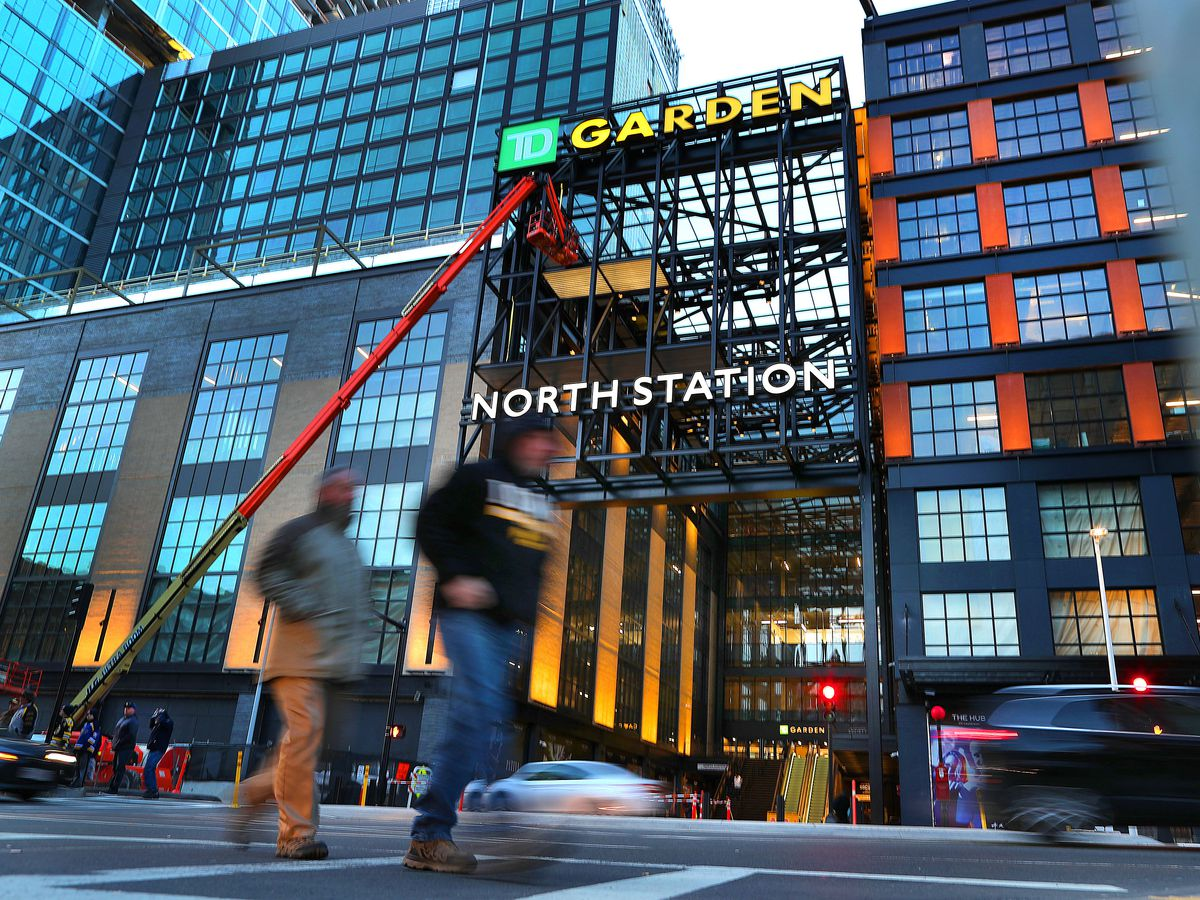 Three large buildings with many windows. In the center is a sign that reads North Station. In the foreground are two people walking quickly.