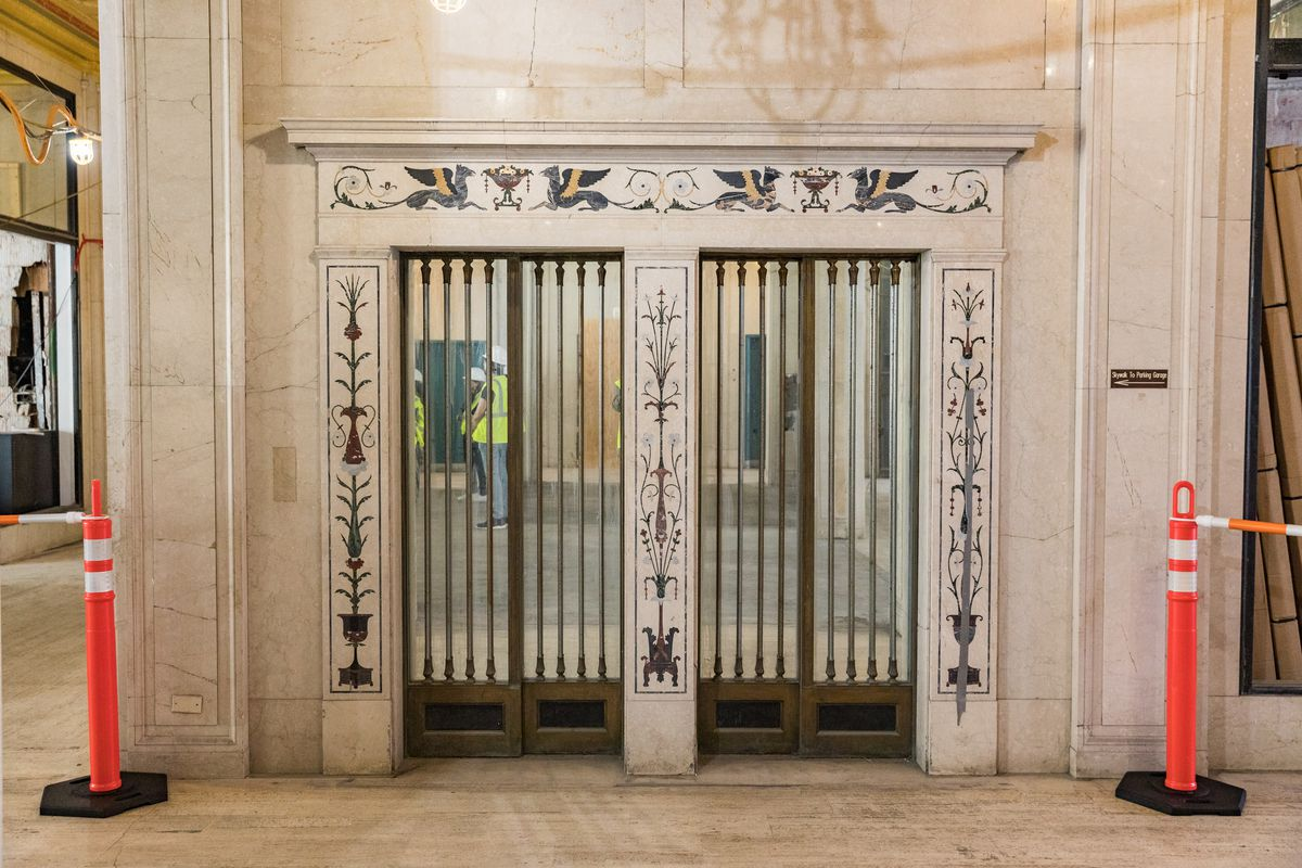 The door frames two adjacent elevators.  Flower patterns are painted on the door frames.