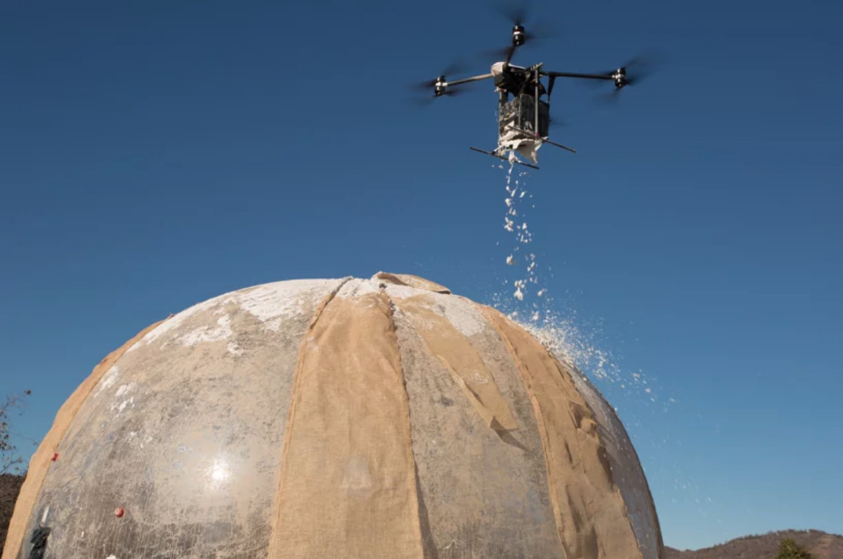 Drone spraying mud on structure
