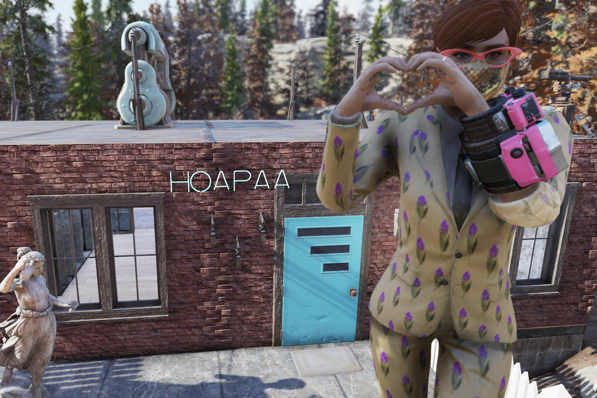 Fallout 76 - a player stands outside their home, posing with their hands in a heart shape.
