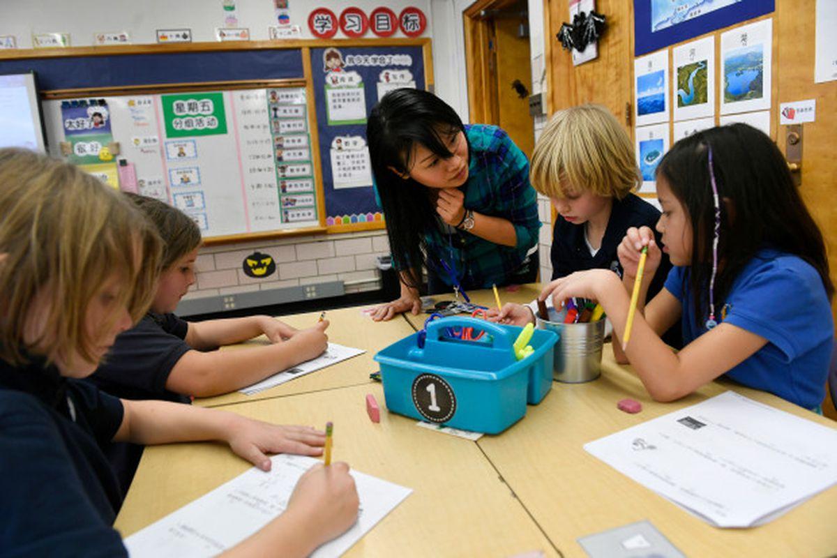 Teacher Yu-Hsin Lien helps her third-grade students with classwork at the Denver Language School.