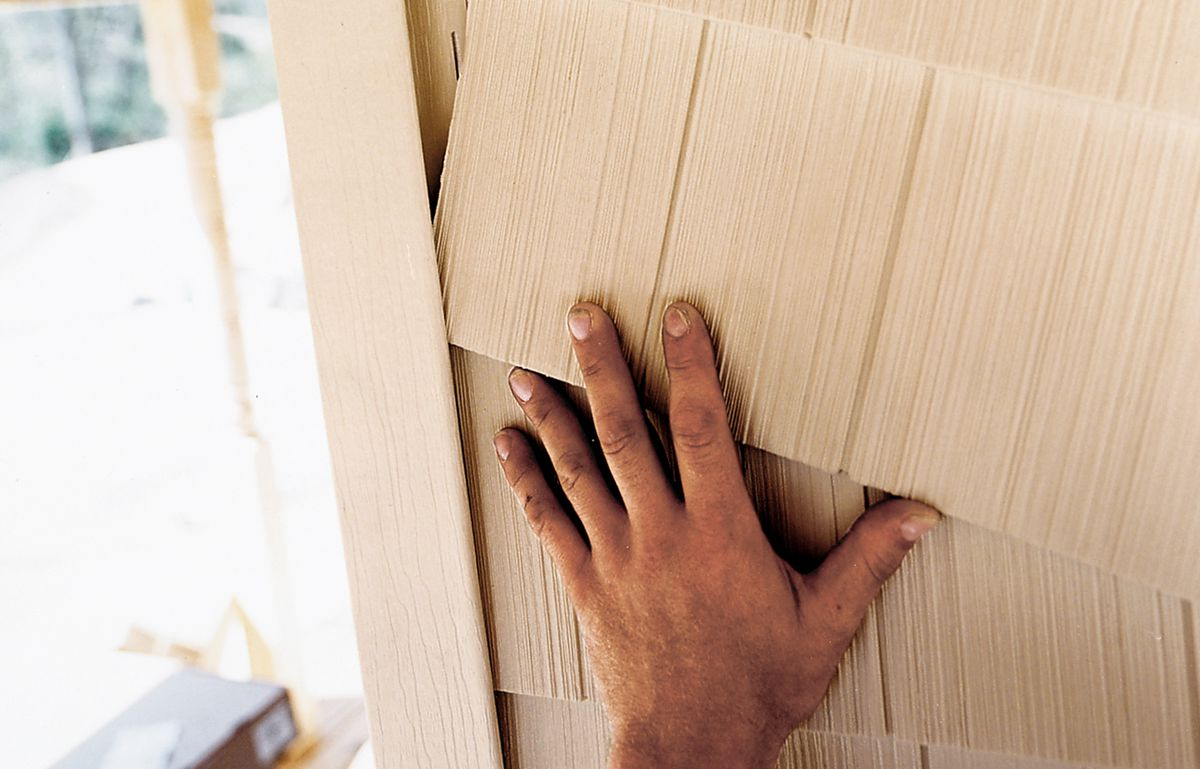 """<p>A panel of polypropylene siding slips into a grooved """"corner board"""" of the same material. Panels expand and contract with temperature changes and shouldn't be installed tight to trim pieces.</p>"""