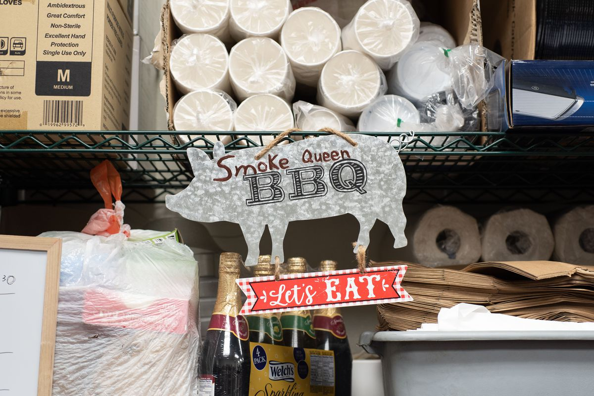 A metal pig sign for Smoke Queen BBQ hangs inside of a dry storage area.