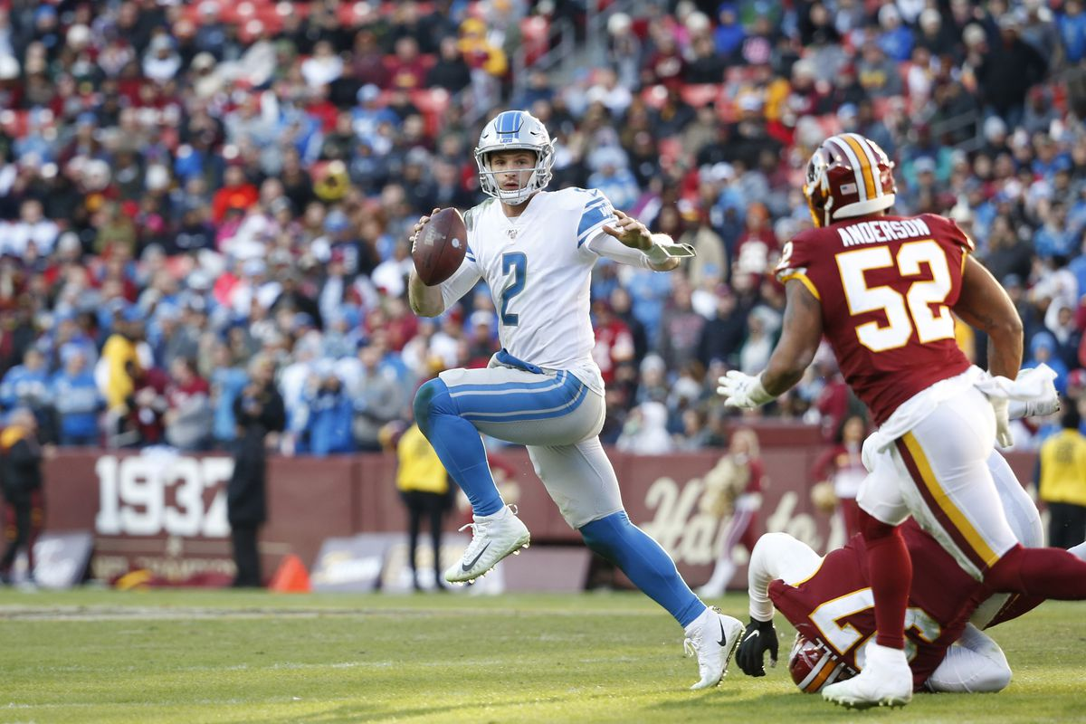 Detroit Lions quarterback Jeff Driskel scrambles with the ball past Washington defensive tackle Tim Settle and linebacker Ryan Anderson during the second half at FedExField.