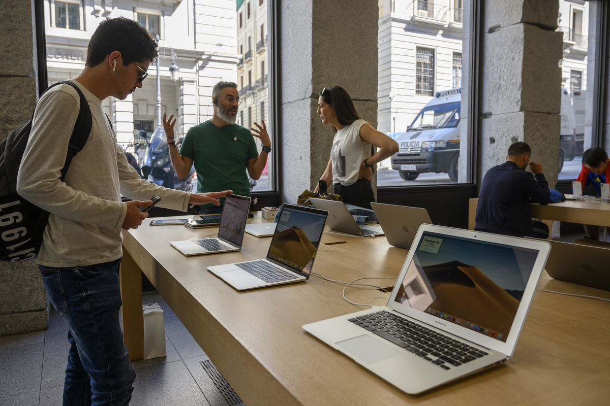 Visitors are briefed about MacBook Air computers on display in the Apple Store at Puerta del Sol square on May 04, 2019 in Madrid, Spain. Apple designs, develops and sells consumer electronics, computer software, and online services, being considered one of the Big Four of technology along with Amazon, Google, and Facebook.