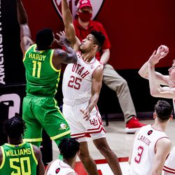 Oregon Ducks guard Amauri Hardy (11) goes to the hoop against Utah Utes guard Alfonso Plummer (25) during the game at the Huntsman Center in Salt Lake City on Saturday, Jan. 9, 2021.