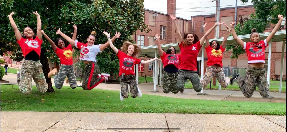 Students simultaneously jump in T-shirts they decorated for a football game outside of Germantown High School.