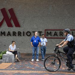Conference attendees and passersby watch as immigrant rights activists protest outside the Marriott Marquis Chicago while U.S. Customs and Border Protection hosts the 2019 Trade Symposium on Tuesday.
