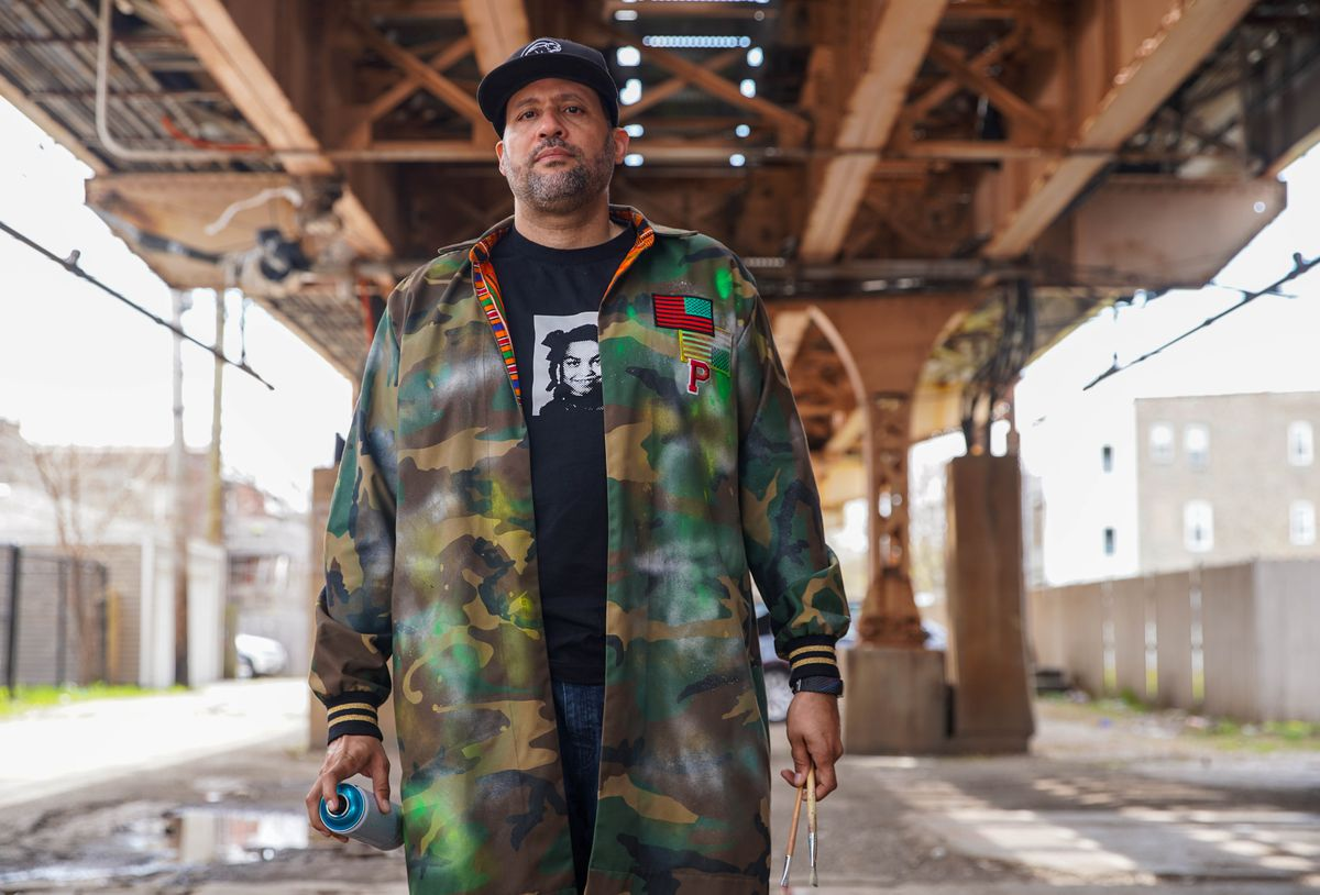 Artist Paul Branton under the CTA Green Line tracks that run above his mural in the 300 block of East 47th Street.