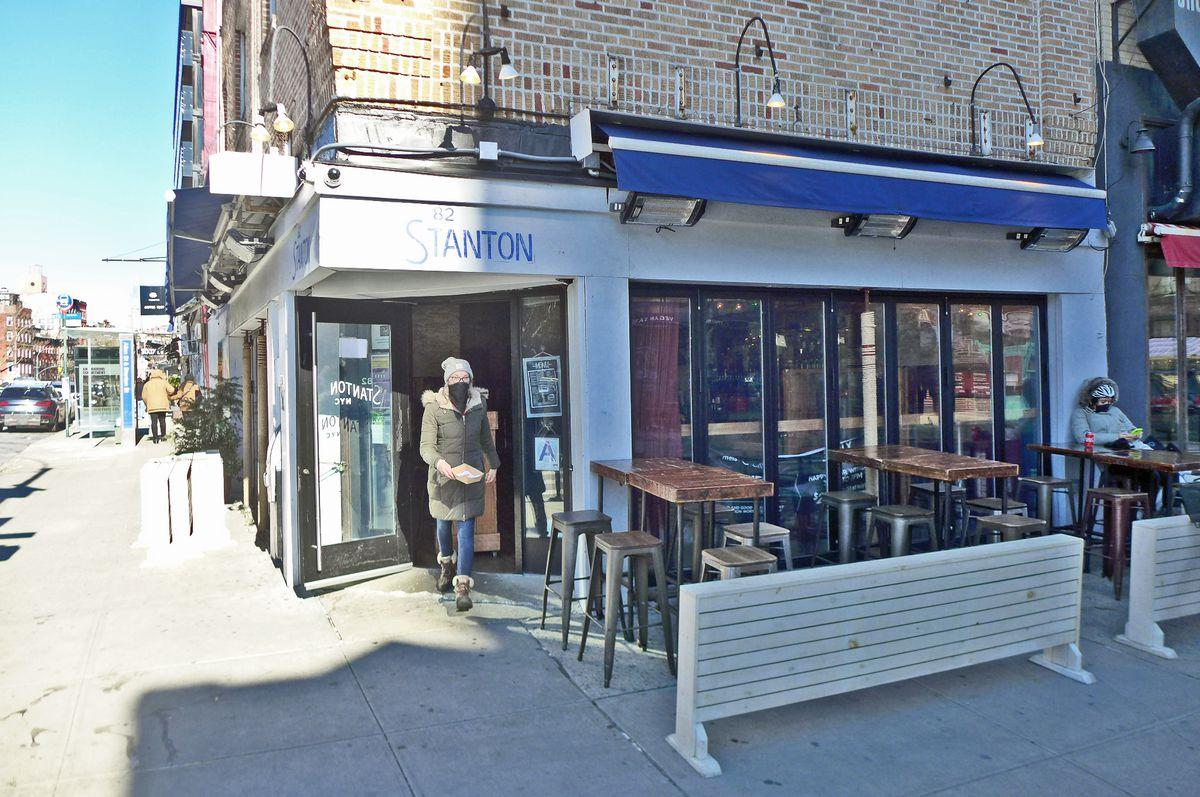 A white bar on the corner with blue trim, half in sunlight, half dark.