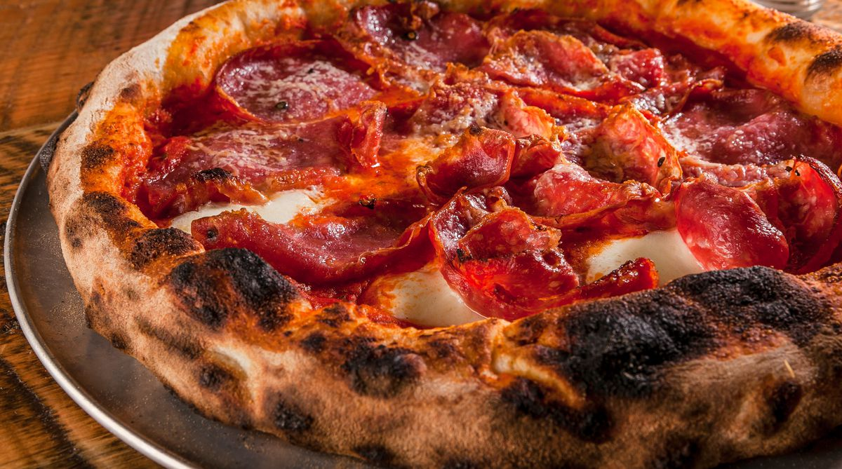 A closeup shot of a soppressata-topped pizza with a puffy, charred crust