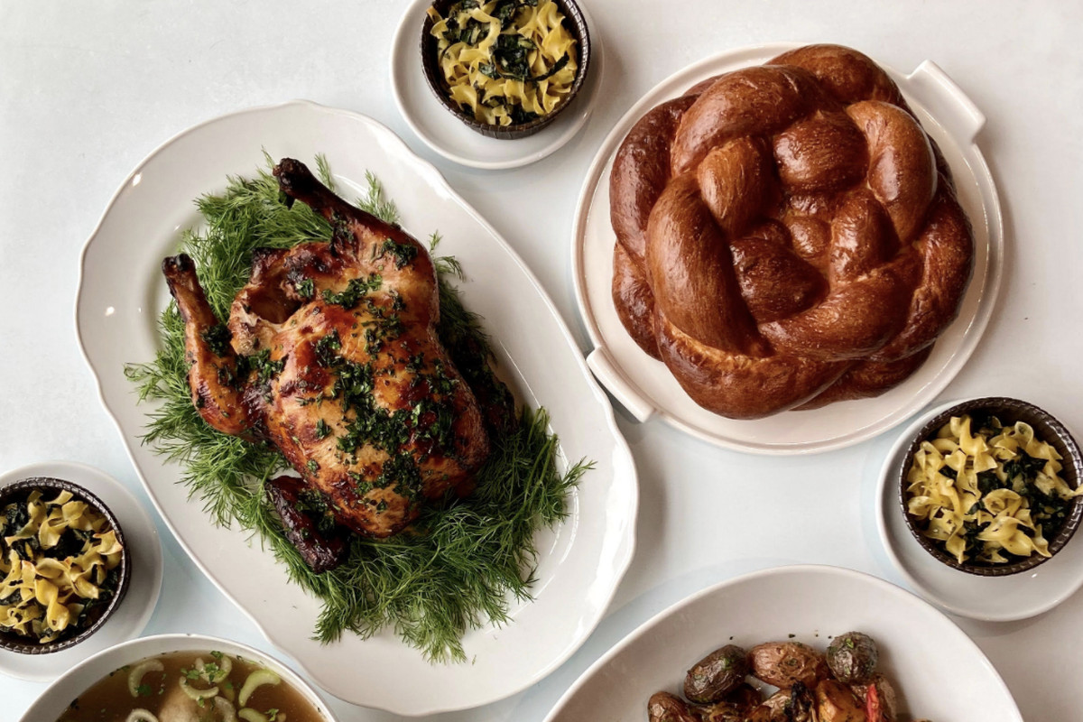 A top-down view of a whole roast chicken covered in herbs, with a challah bread to the right and a variety of sides
