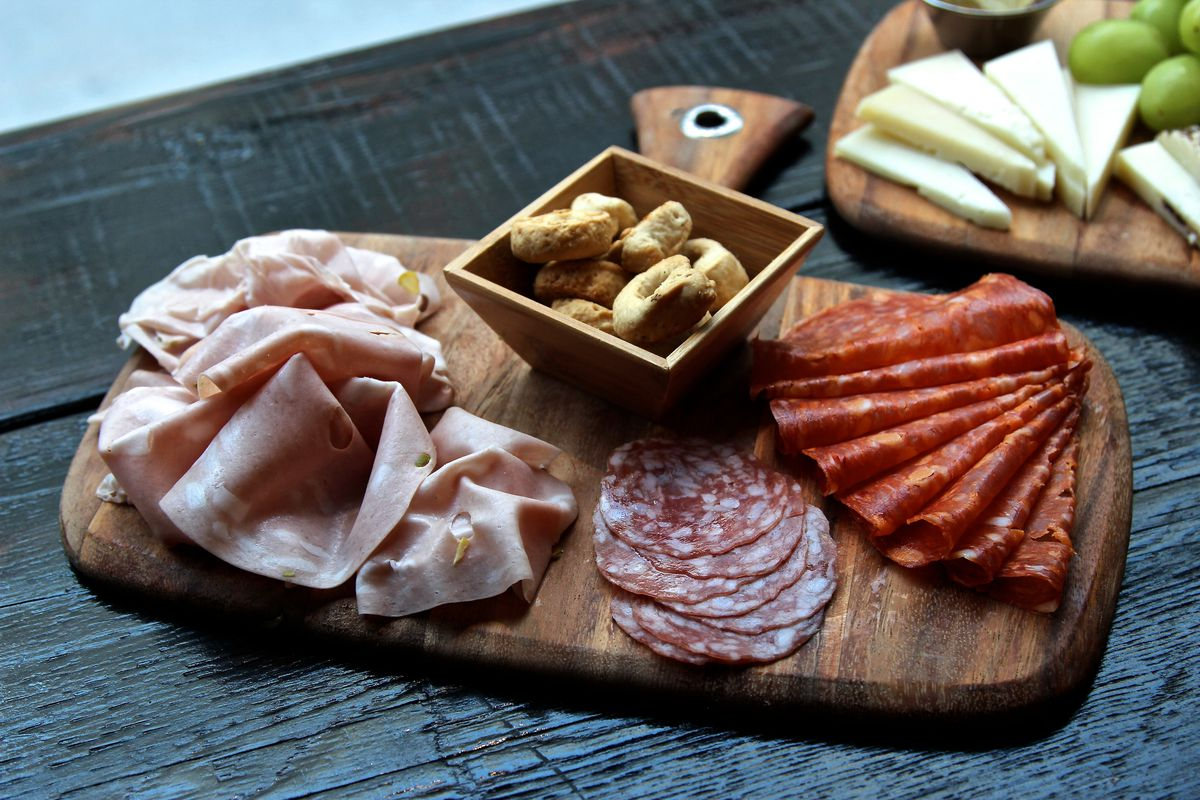 A cheeseboard carrying three different types of Italian salamis